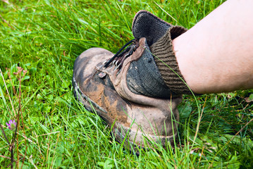 Duty old mountain boots have a rest at grass after activity