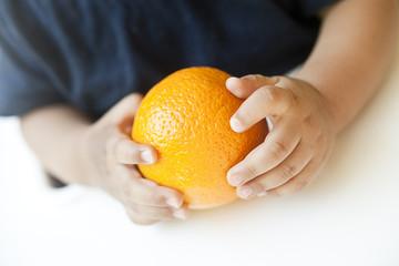 Babyhände greifen eine Orange
