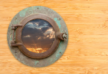 Antique Porthole with View of Sunset on Bamboo Wall