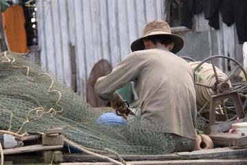 Fisherman mending his fishing net