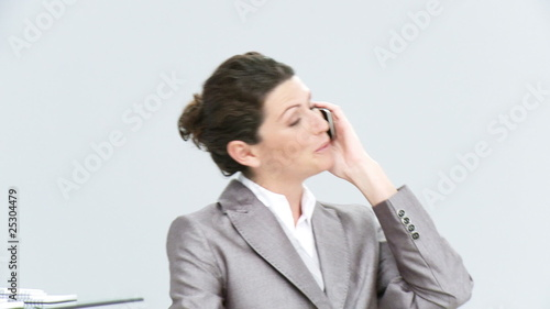 joyful businesswoman speaking on phone sitting in her office