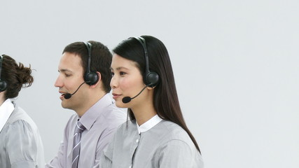 people working in a call-center with asian woman looking camera