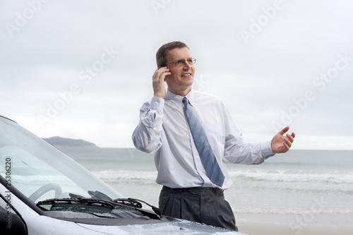 Lächelnder Geschäftsmann mit Handy am Strand
