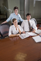Three office workers working in boardroom