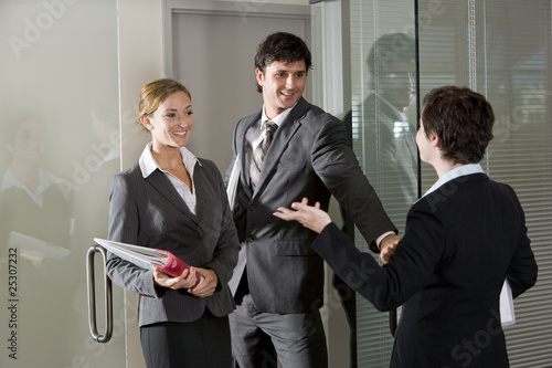 Three office workers chatting at door of boardroom