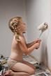 Девочка с косичками усердно красит стену белой краской