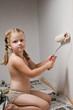 Девочка в трусиках валиком красит стену белой краской