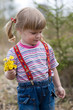 Русоволосая девочка с хвостиками собирает цветы на улице