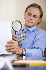 Businessman reading fine print in contract with magnifying glass