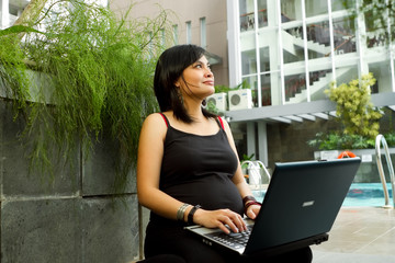 Asian pregnant business woman working with laptop