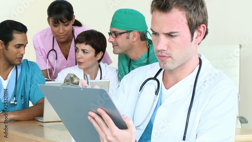Concentrated doctor looking notes with his team in background