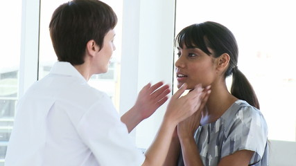Female doctor examining a patient's throat