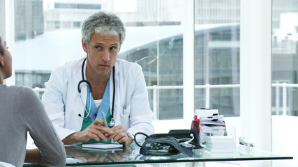 male doctor discussing with an afican patient