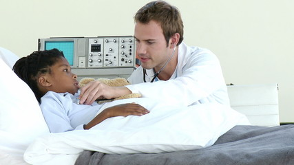 young doctor visiting young boy at the hospital