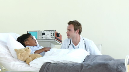 doctor visiting young boy in his room