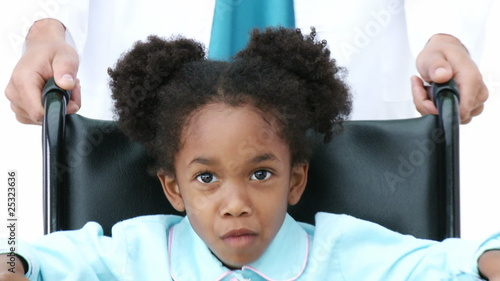 portrait of an african little girl sitting in a wheelchair