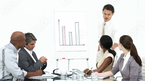 hispanic businessman showing graphs to his team