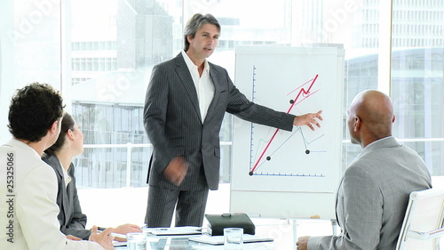 confident business man reporting figures to his young team