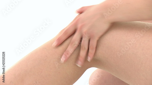 Attractive woman massaging her knee against a white background