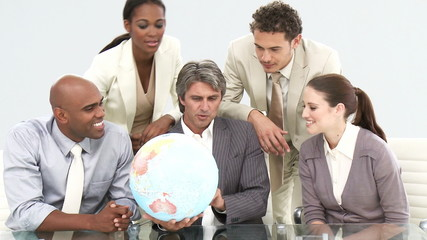 Multi-cultural business team looking at a terrestrial globe