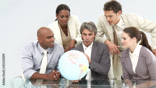 multi-ethnic team watching a terrestrial globe