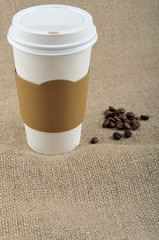 Disposable coffee cup on jute background with copy space.