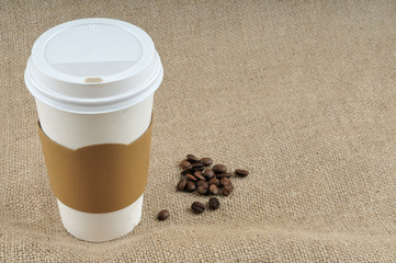 Paper coffee cup on jute background with copy space.