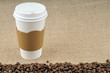 Paper coffee cup with safety cardboard collar on jute background