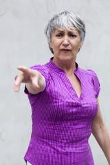 femme senior index levé  accusation  médisance
