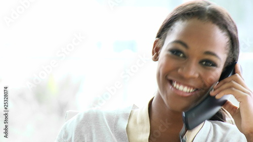smiling businesswoman speaking on phone in her office