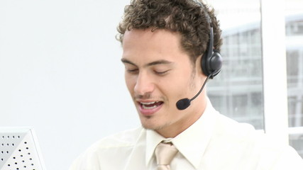 hispanic man working in a call center with headset on