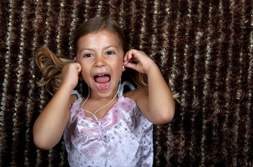 Little girl listening to music on headphones and cheering