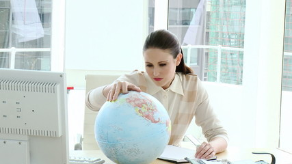 attractive businesswoman looking at a globe in her office
