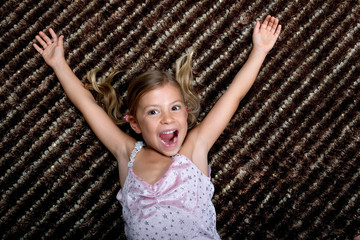 Little girl lying on a rug and cheering with delight