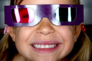 Little girl wearing 3D glasses and watching a film