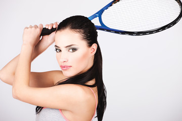 Female tennis player holding racket behind head