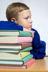 young boy with hand on top of books