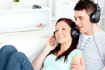 Charming caucasian couple listening to music wearing headphones