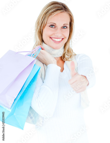 Delighted woman with thumb up holding shopping bags