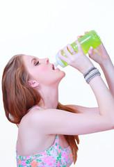 Girl drinking water from plastic bottle