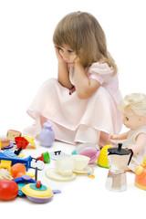 The sad girl among toys