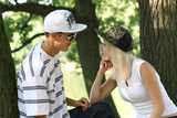 young girl and a guy talking in caps