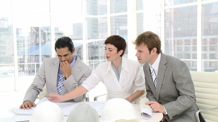 businessmen and businesswoman watching plans in office