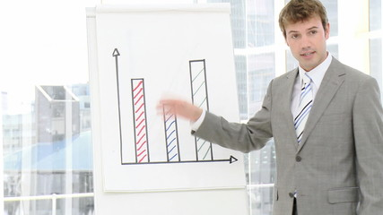 young businessman showing graphs during meeting