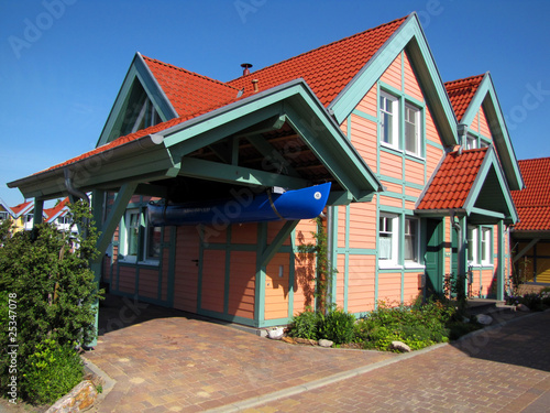 wooden house with carport and boat - 25347078