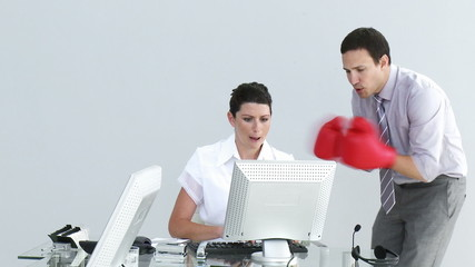 businessman talking to his colleague wearing boxing gloves