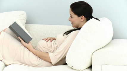 pregnant woman lying on he couch reading a book