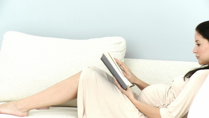 pregnant woman reading in her sofa