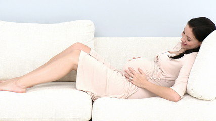 pregnant holding her belly lying in the couch