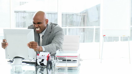 upset african businessman looking at computer